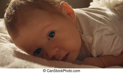 Baby girl trying to crawl on the bed