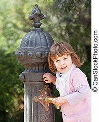 Baby girl using water pump on street of Barcelona