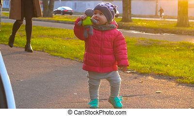 Baby girl walking and playing with toy in the park on a...