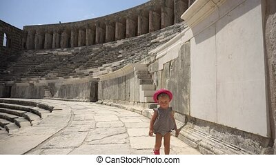 Baby girl walking in ancient amphitheatre in hot summer day
