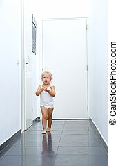 Baby girl walking in hallway at home