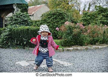 Baby girl walking in the garden, autumn