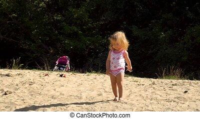 Baby girl walking on sandy beach