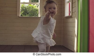 Baby girl walking through the house - Baby girl in white...