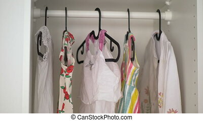 Baby girl wardrobe - Little girl clothes on the hangers in...