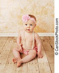 Baby girl wearing pearls