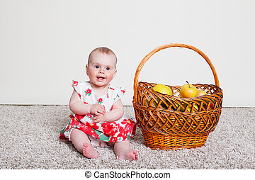 baby girl with a basket of Green apples
