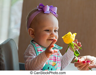 Baby girl with a flower smiling
