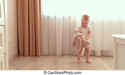 Baby girl with a toy rabbit having fun in the room. - Child ...