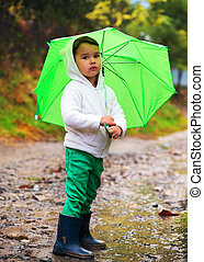 baby girl with an umbrella in the rain runs through the puddles playing on nature