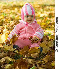 baby girl with autumnal leaves