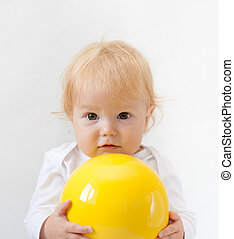 Baby girl with bright yellow ball
