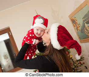 Baby girl with Christmas suit playing with her mom.