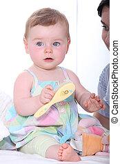 Baby girl with hairbrush