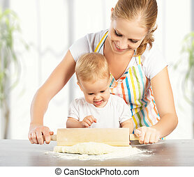 baby girl with her mother rolled out the dough cook, bake