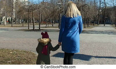 Baby girl with mom running in a park and waving hands