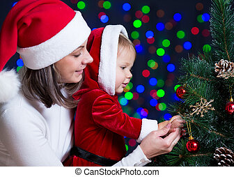 baby girl with mother decorating Christmas tree on bright background