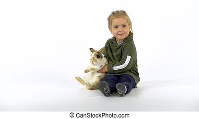 Baby girl with pigtails is stroking fluffy three colored rabbit at white background. Slow motion.