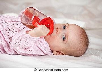 Baby girl of 5 months with sippy cup on white blanket