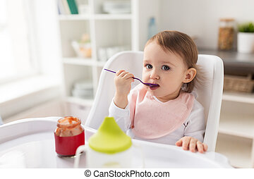 baby girl with spoon eating puree from jar at home - food,...