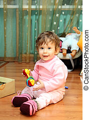 baby girl with toy on floor