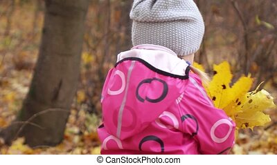 Baby girl with yellow leaves - In autumn park girl collects...