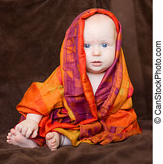 Baby girl wrapped in orange scarf