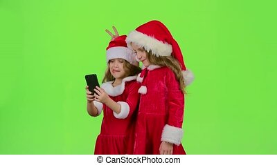 Baby girls in New Year costumes do selfie on the phone. Green screen. Slow motion