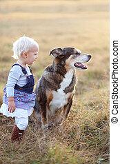 Baby Girls Talking to German Shepherd Dog Outside at Sunset