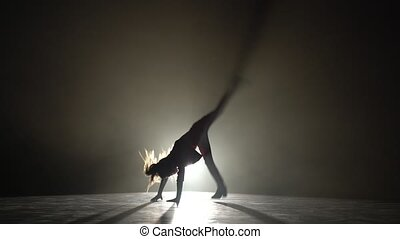 Little child does a handstand in the studio. Black smoke background. Silhouette. Light from behind