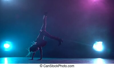 Little child does a handstand in the studio. Multicolor smoke background. Silhouette. Light from behind. Slow motion