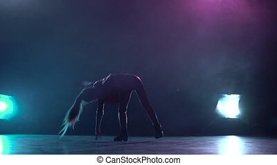 Little child does a handstand in the studio. Multicolor smoke background. Silhouette. Light from behind