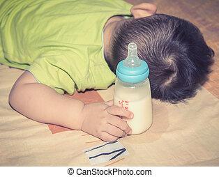 Baby hand hold milk bottle , vignette