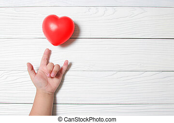 Baby hand supporting with a red heart.