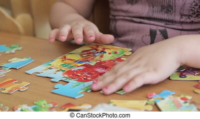 Baby hand to collect the puzzle on the table