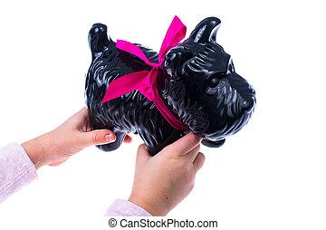 Baby hands, black toy dog. Studio Photo