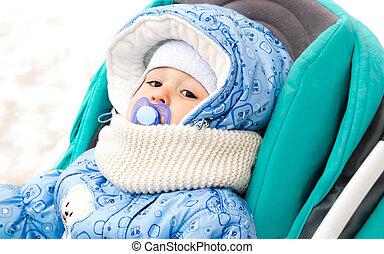 baby happy laughing enjoying a walk in a snowy winter park sitting in a warm stroller with sheepskin hood