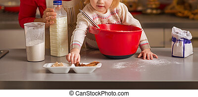 Baby helping mother make christmas cookies in christmas decorate