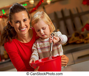 Baby helping mother make christmas cookies