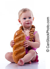 Baby holding a loaf of bread