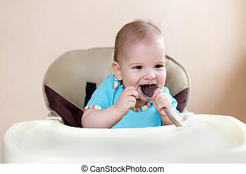 baby holding a spoon in his mouth and laughs