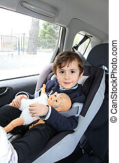 Baby holding his doll, in car seat