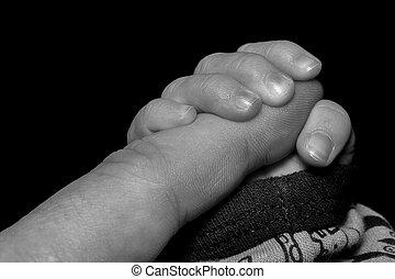 Baby Holding Index Finger Close up on black background.
