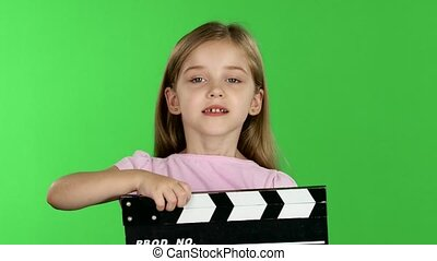 Baby holds in hands clapperboard. Green screen - Child girl...