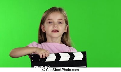 Baby holds in hands clapperboard. Green screen. Slow motion
