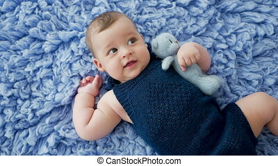 baby in a blue knitted jumpsuit clothes lying on blue fur