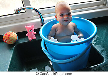 Baby in a Bucket - A baby in a blue bucket cools off in the...