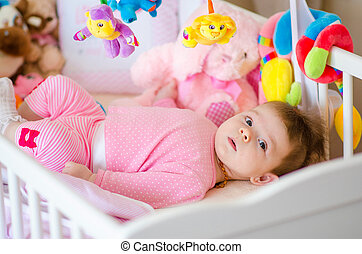baby in a cot - little cute baby girl playing in a cot