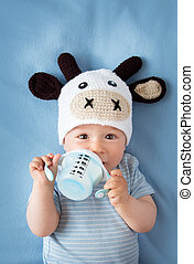 Baby in a cow hat drinking milk