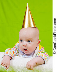Baby in a golden holiday cap on a green background